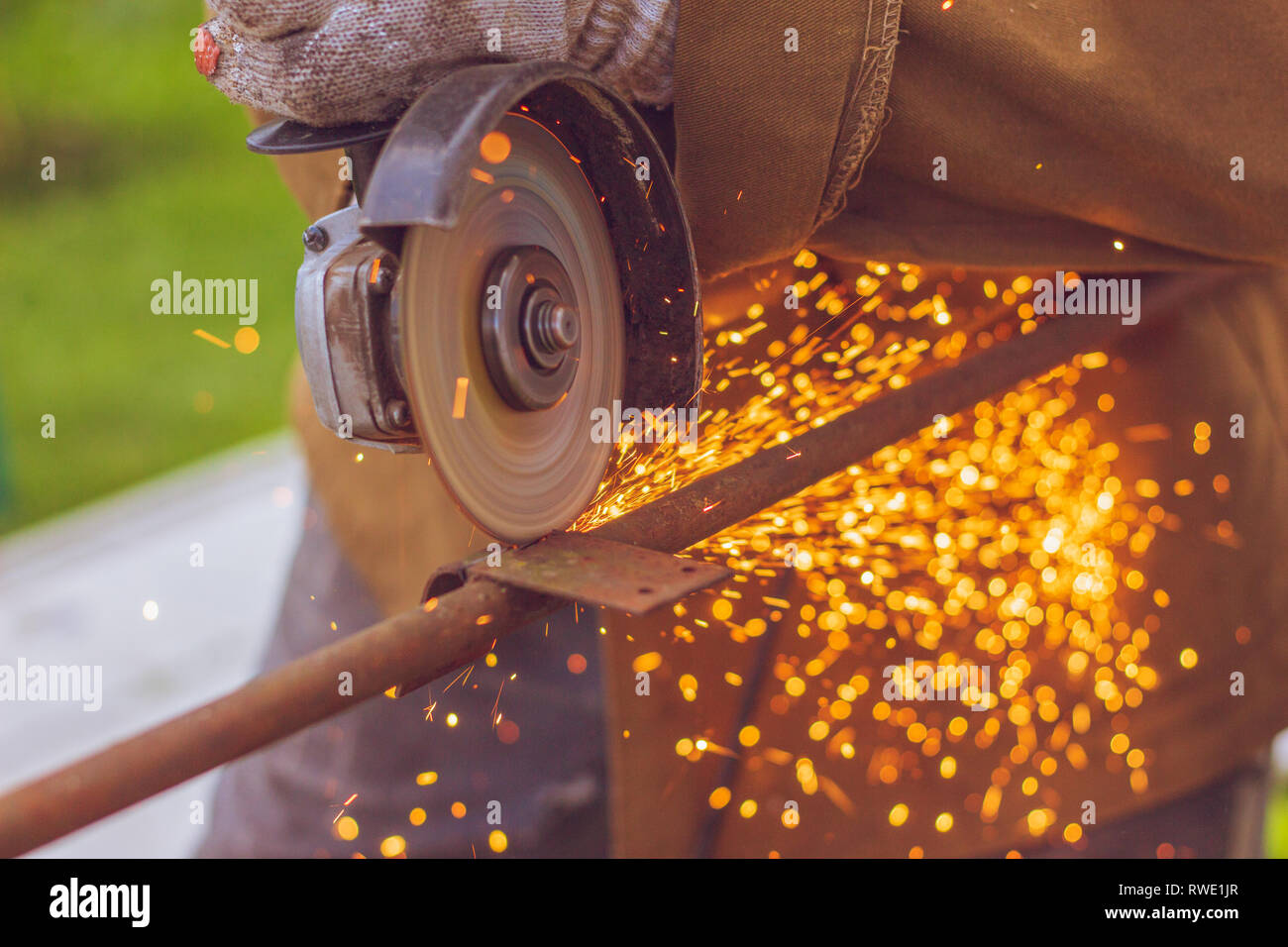 Cutting blade grinder close-up with flying sparks from the metal during the cutting process - Stock Image