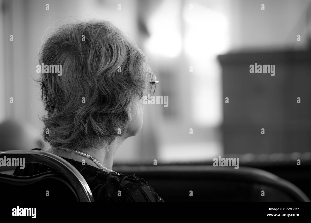 Back view of old woman sit on chair. Elderly people depressed and anxiety. Aging society depression problem in senior retirement person. Alzheimer and - Stock Image