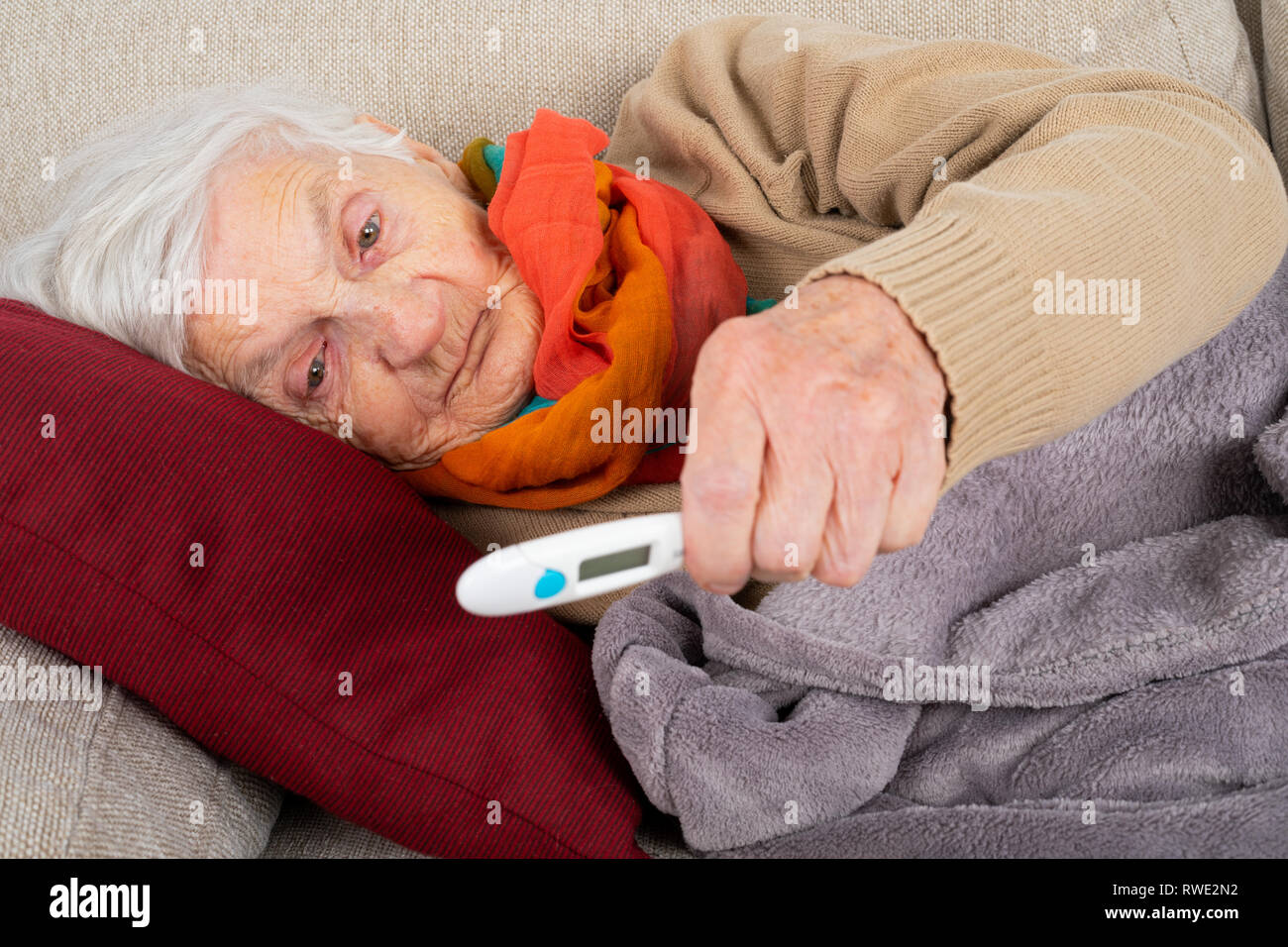 Elderly sick woman lying on the couch holding digital thermometer in her hands - fever, influenza, pneumonia - Stock Image