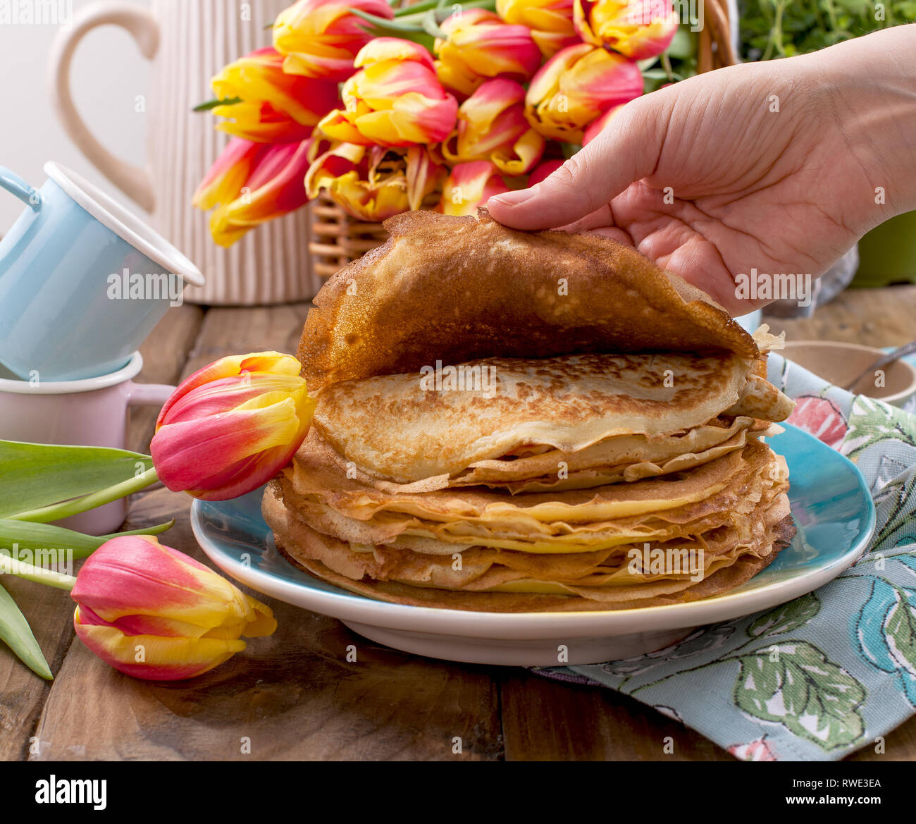 Pancakes With Caviar And Butter In A Woman S Hand A Bouquet Of Fresh Tulips And A Wooden Background Traditional Russian Food For Carnival Stock Photo Alamy
