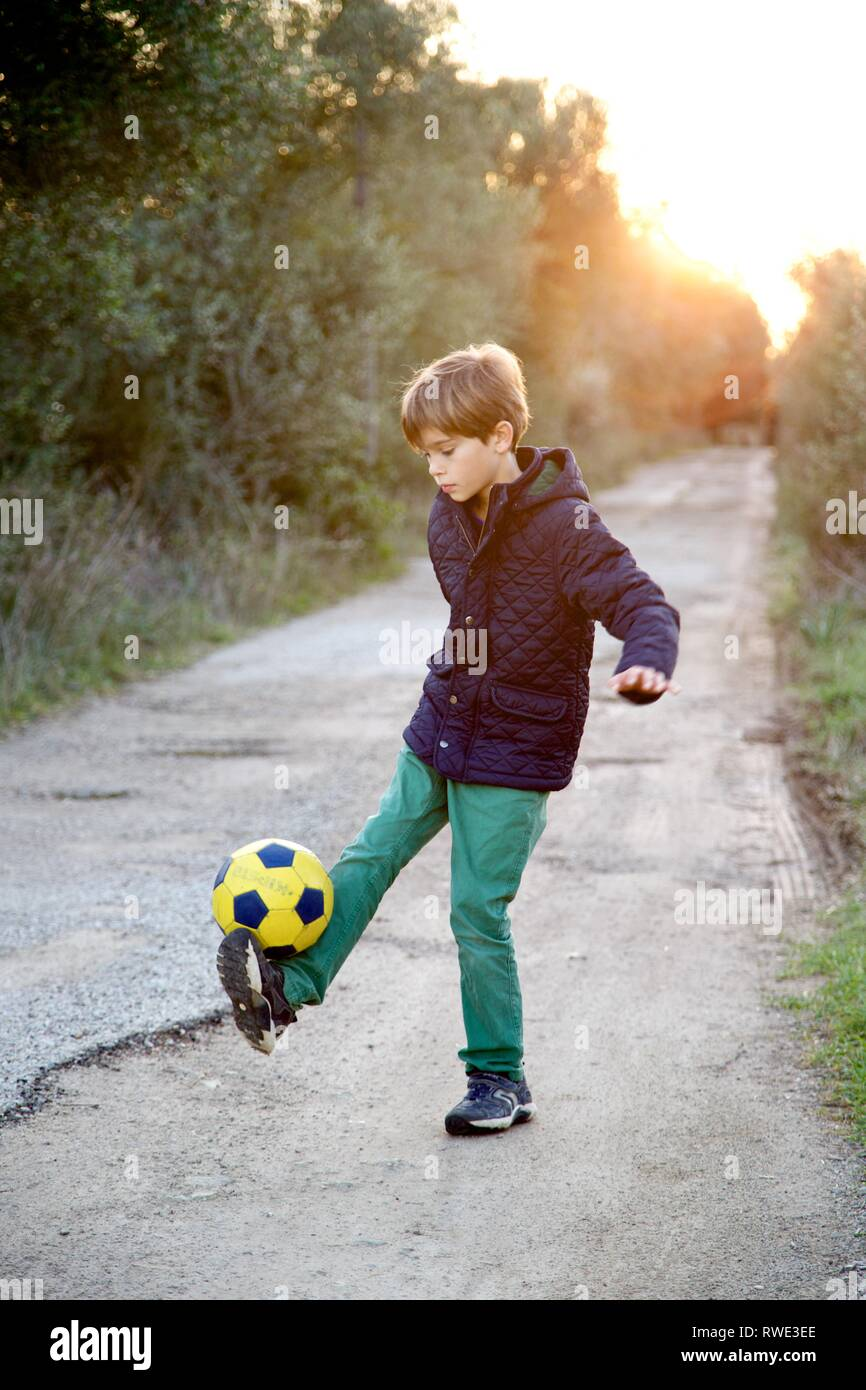 Young boy having fun playing football at sunset - Stock Image