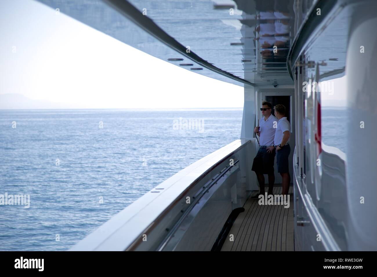 Wide view of 2 Superyacht crew in uniform on deck talking, sea background - Stock Image