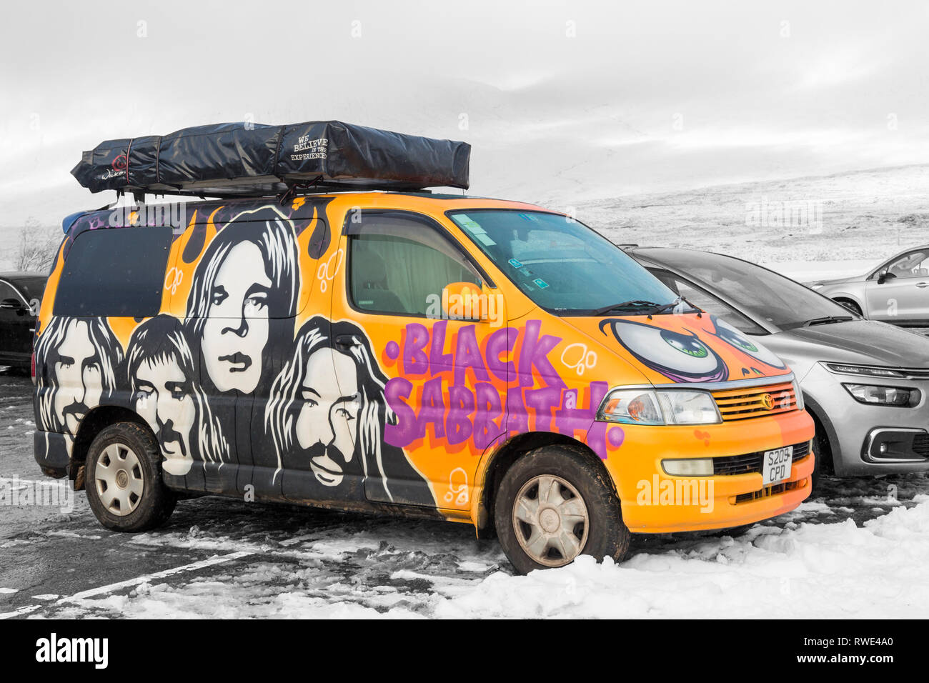 3689245363 Wicked Campers Black Sabbath painted campervan parked in snow covered car  park at Glencoe mountain resort