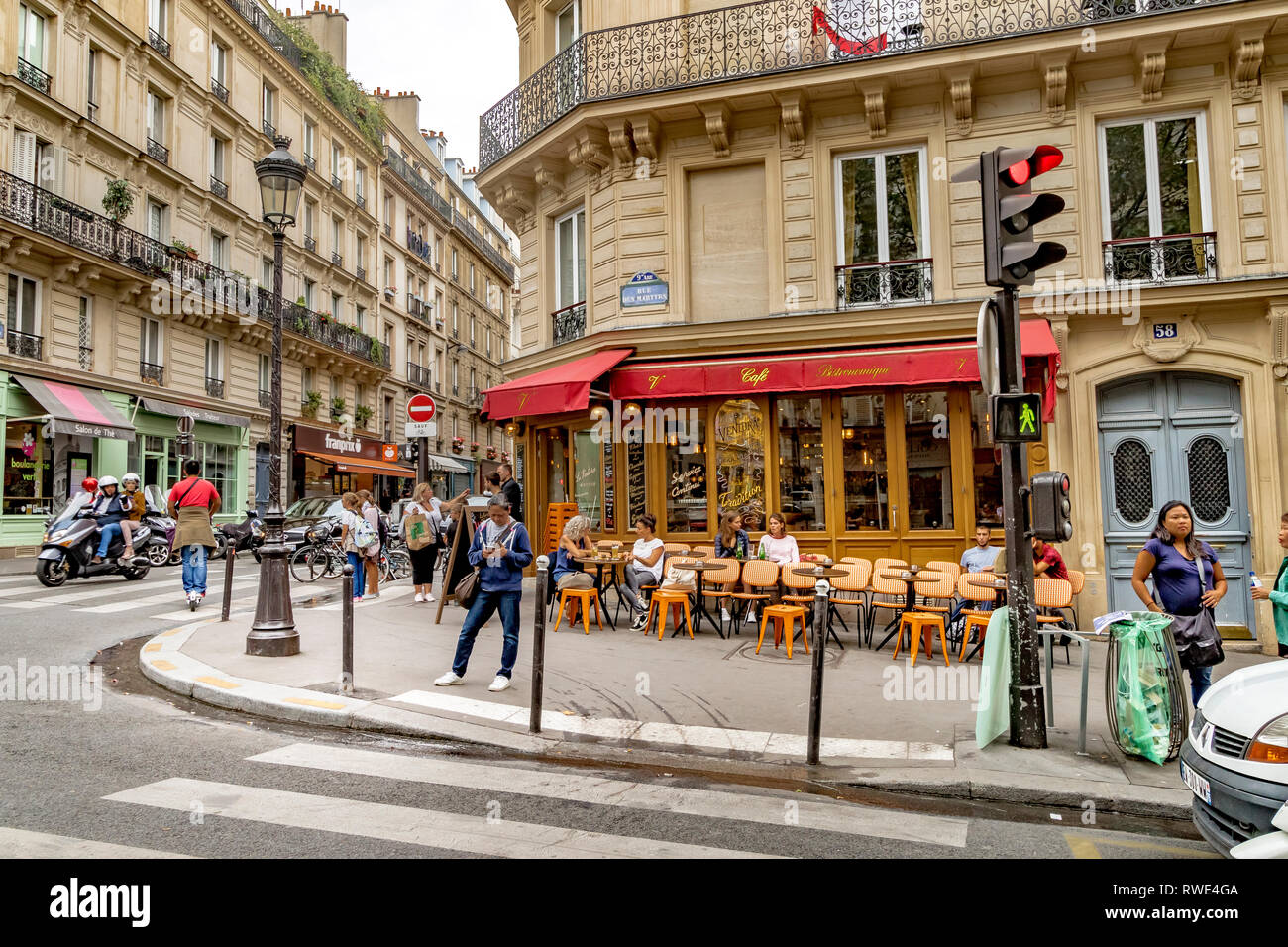 A woman looks at her mobile phone standing outside Le Ventura restaurant cafe on Rue des Martyrs in Monmartre in the 9th arrondissement of Paris - Stock Image