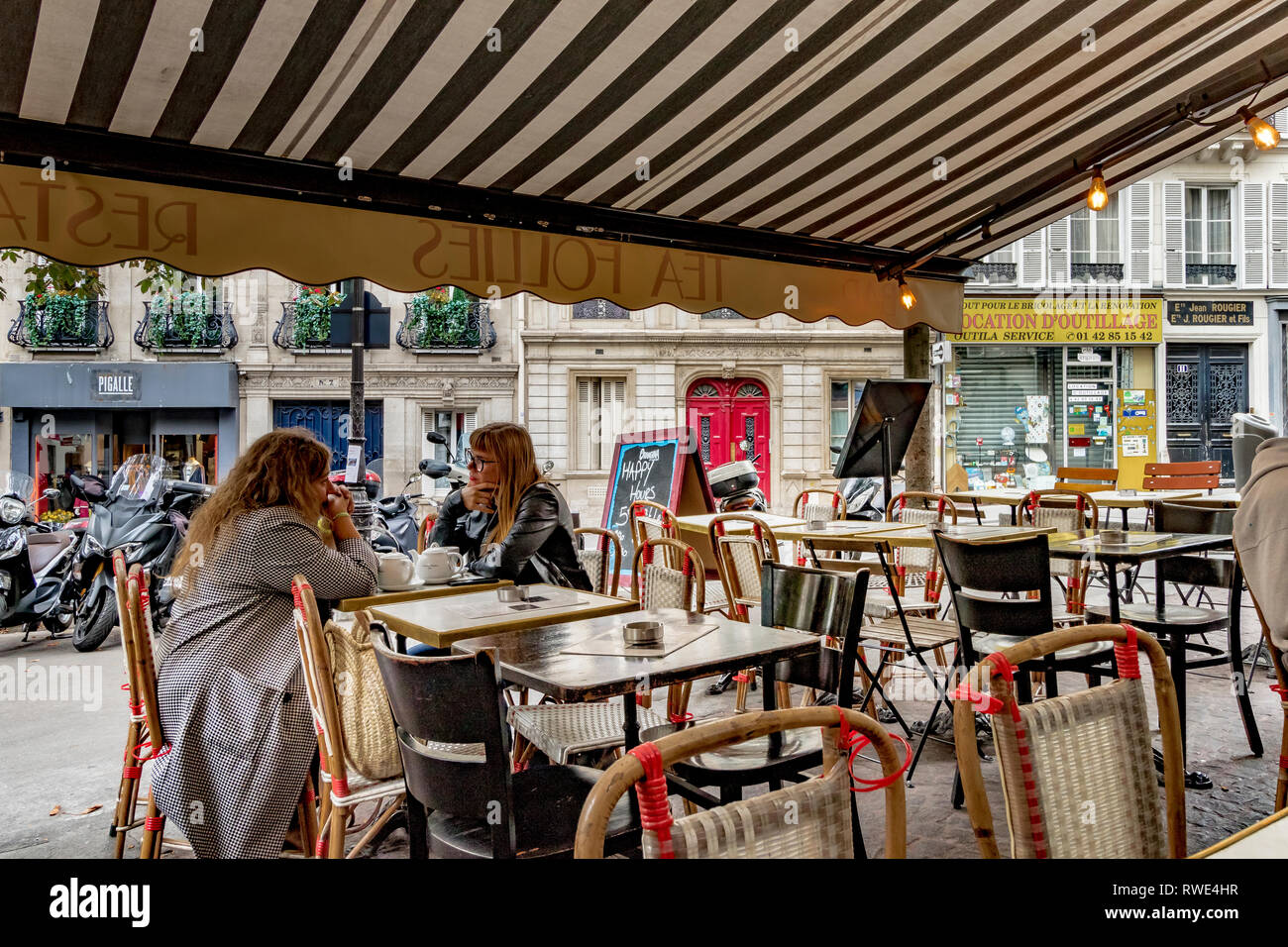 Two woman talking and enjoying a pot of tea at a restaurant in St Georges in the 9th arrondissement of Paris Stock Photo