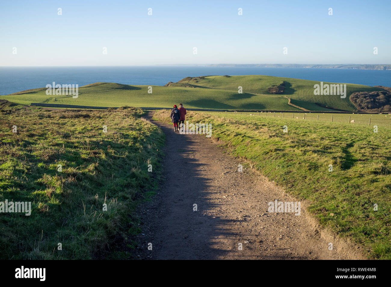 Friends walking along the headland of Bolt Tail, a spectacular coastal walk from Bolberry Down to Hope Cove on the South Devon Coast, UK - Stock Image