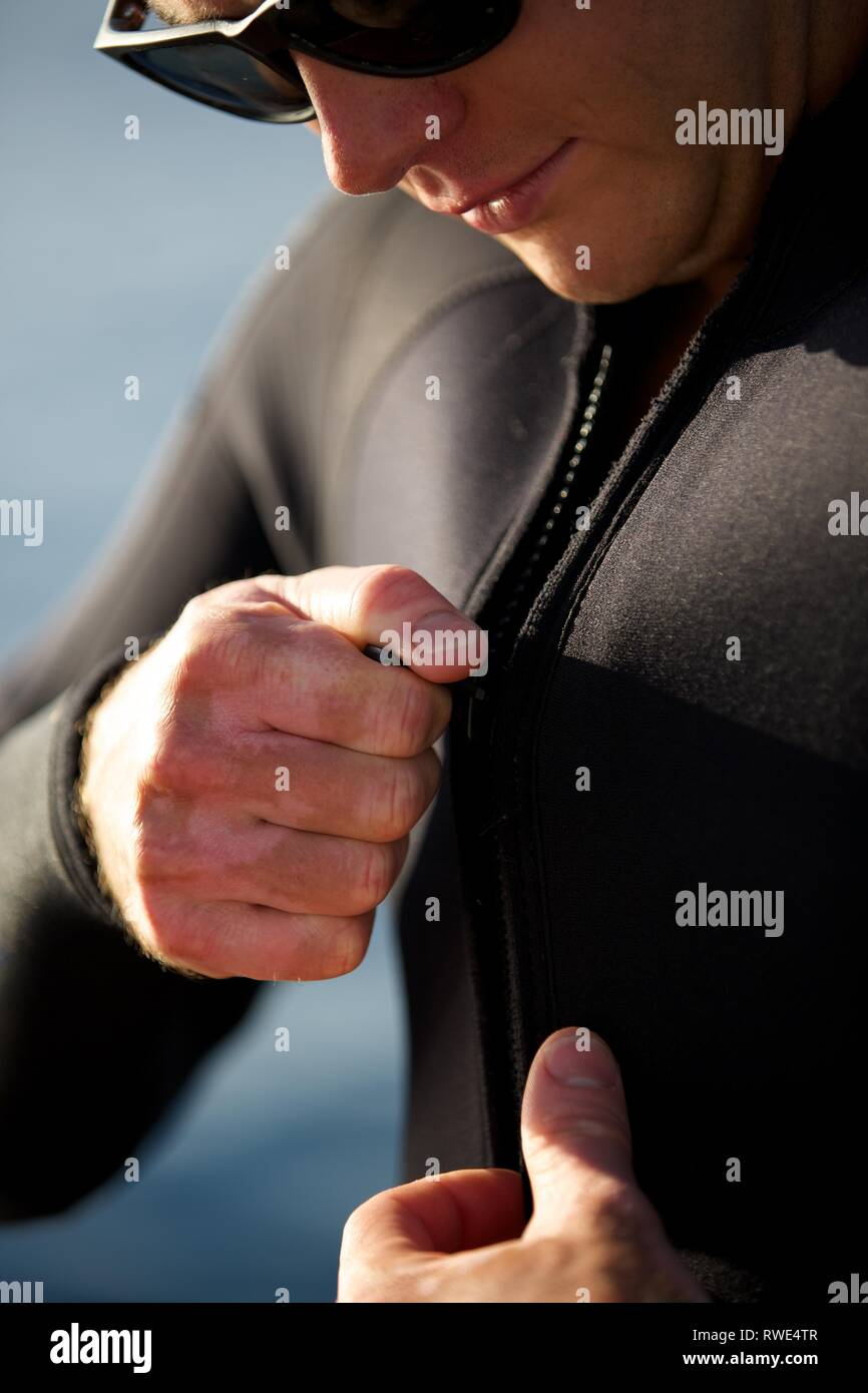 Close up of handsome diver in sunglasses doing up his wetsuit - Stock Image