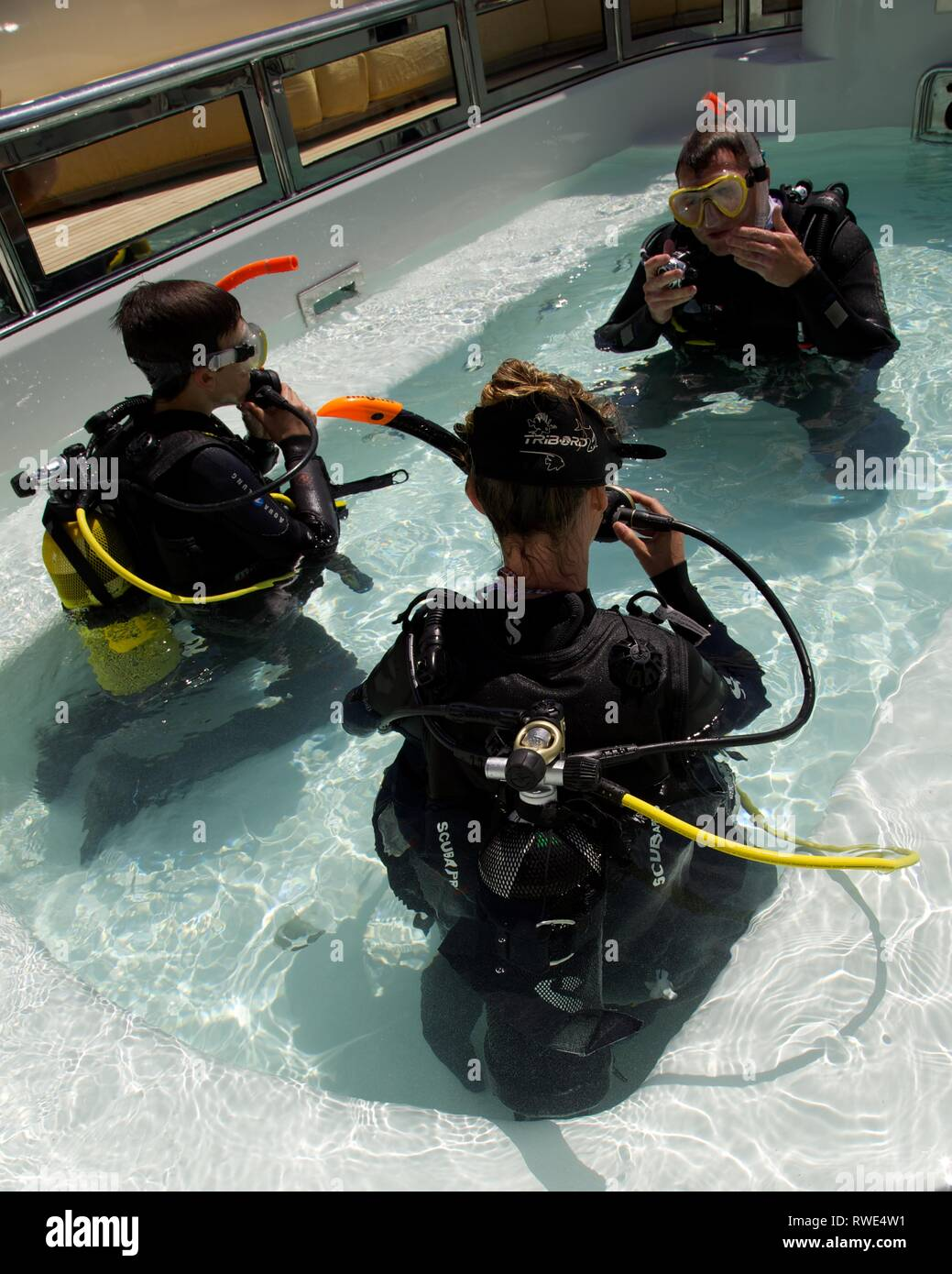 Group of three divers in a pool learning to dive - Stock Image