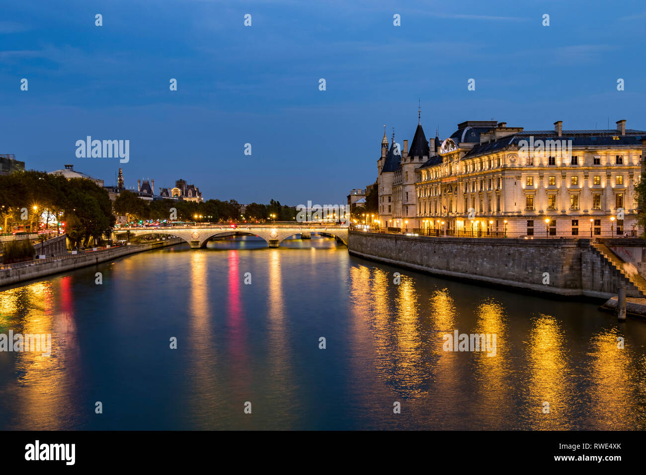Lights reflecting off The River Seine at night  from Pont Neuf, with Pont au Change and The Turrets of The Conciergerie on the Île de la Cité ,Paris - Stock Image
