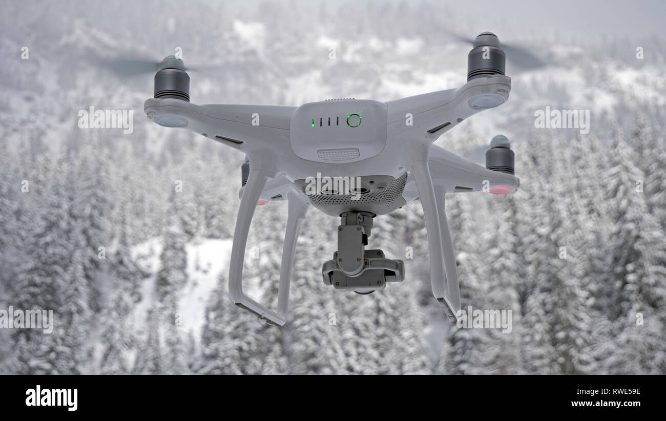 A drone hovers in flight in front of the Camera against a snow white forest alpine background. The drone is close up in the foreground. Stock Photo