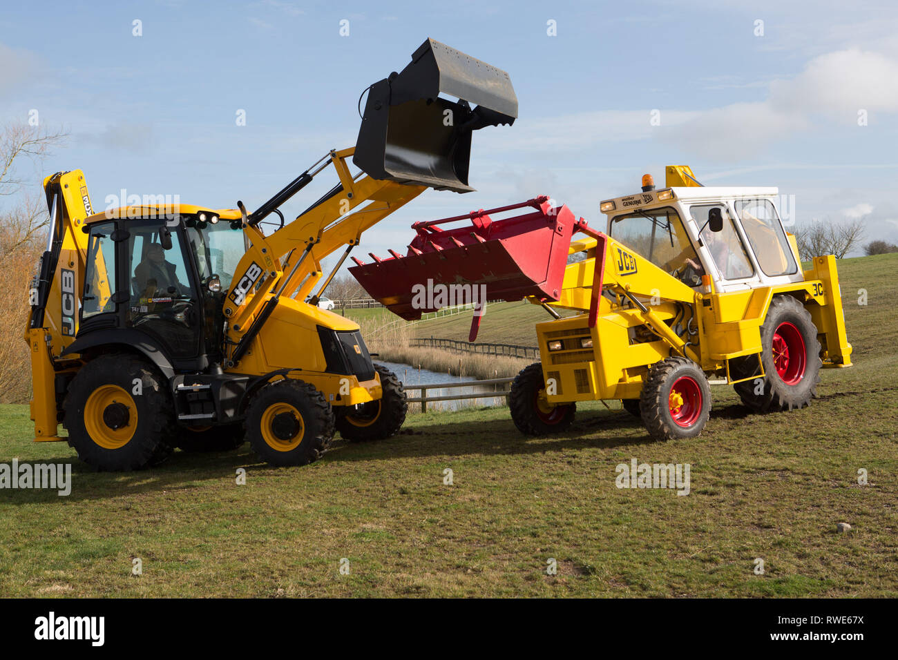 The model that made JCB great - The 3c (on the right) backhoe loader with it's modern counterpart - Still built at Rocester, Staffs UK - Stock Image