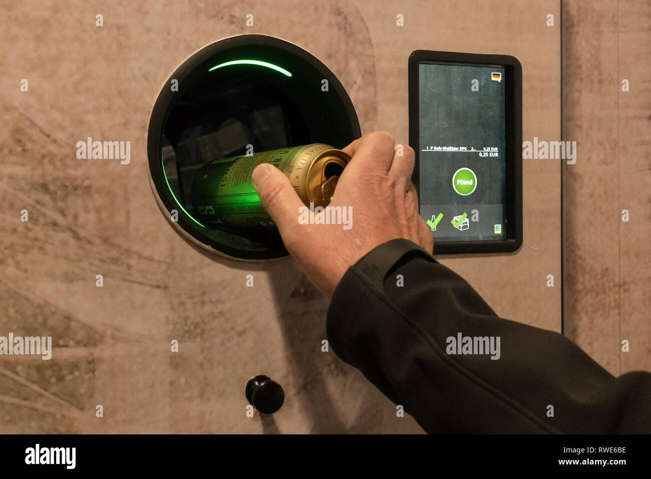 Pfand System in Germany - man putting a drinks can into a reverse vending machine pfandautomat to receive a credit refund for the deposit paid - Stock Image