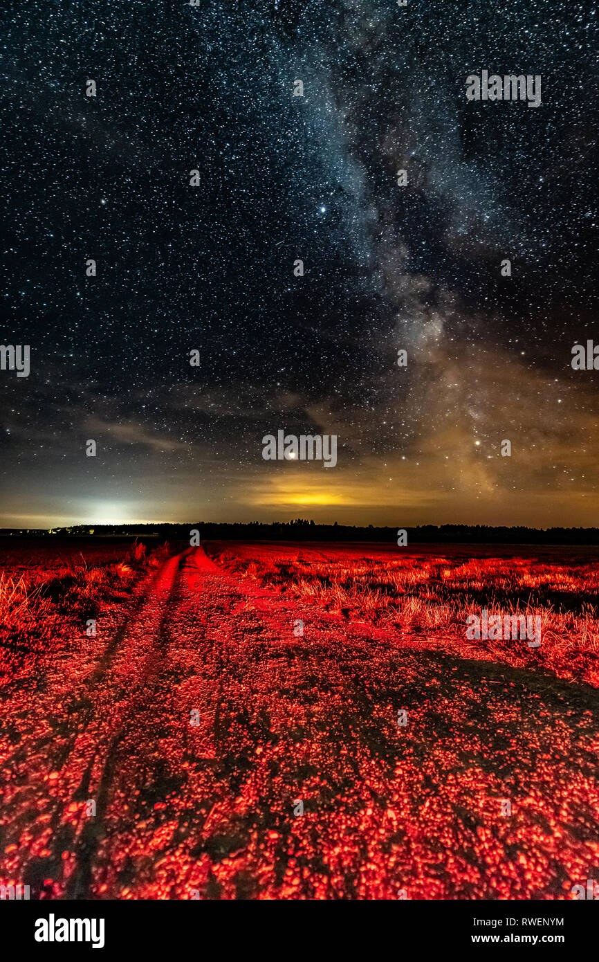 Night Starry Sky With Milky Way Glowing Stars And Country Road - Stock Image