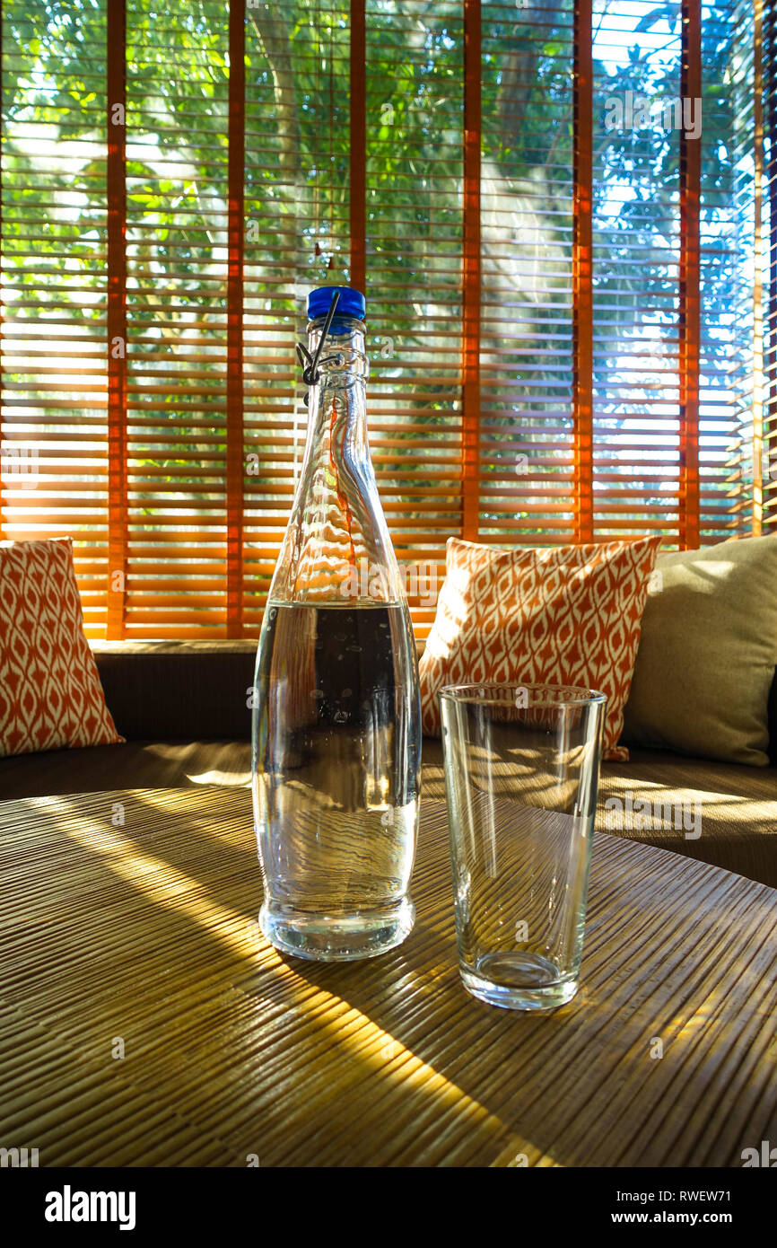Elegant Glass Water bottle on Resort room table, with natural lighting and couch cushions, Panglao - Bohol, Philippines - Stock Image