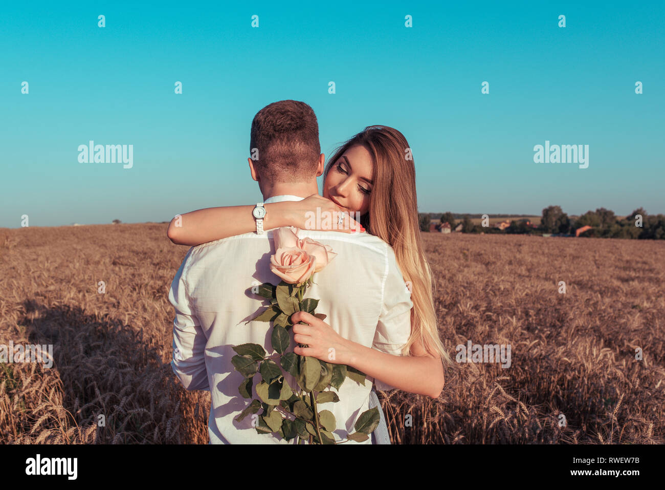 The girl in a dress, hugs man guy, with a bouquet of rose flowers. The concept of the gift, the unexpectedness of love and joy. Emotions of happiness - Stock Image