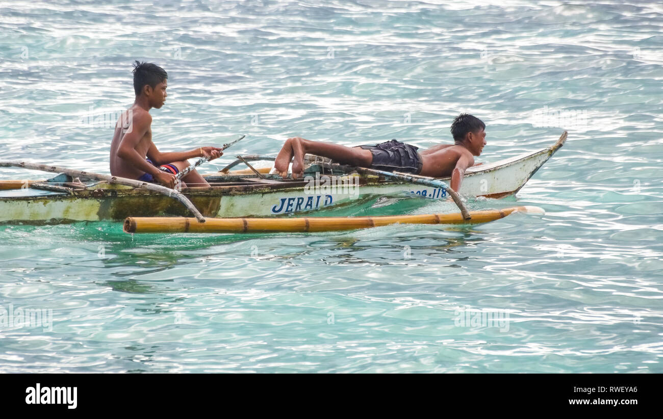 Young Fishermen Boys in Boat on Sea - Boracay Island, Panay - Philippines - Stock Image
