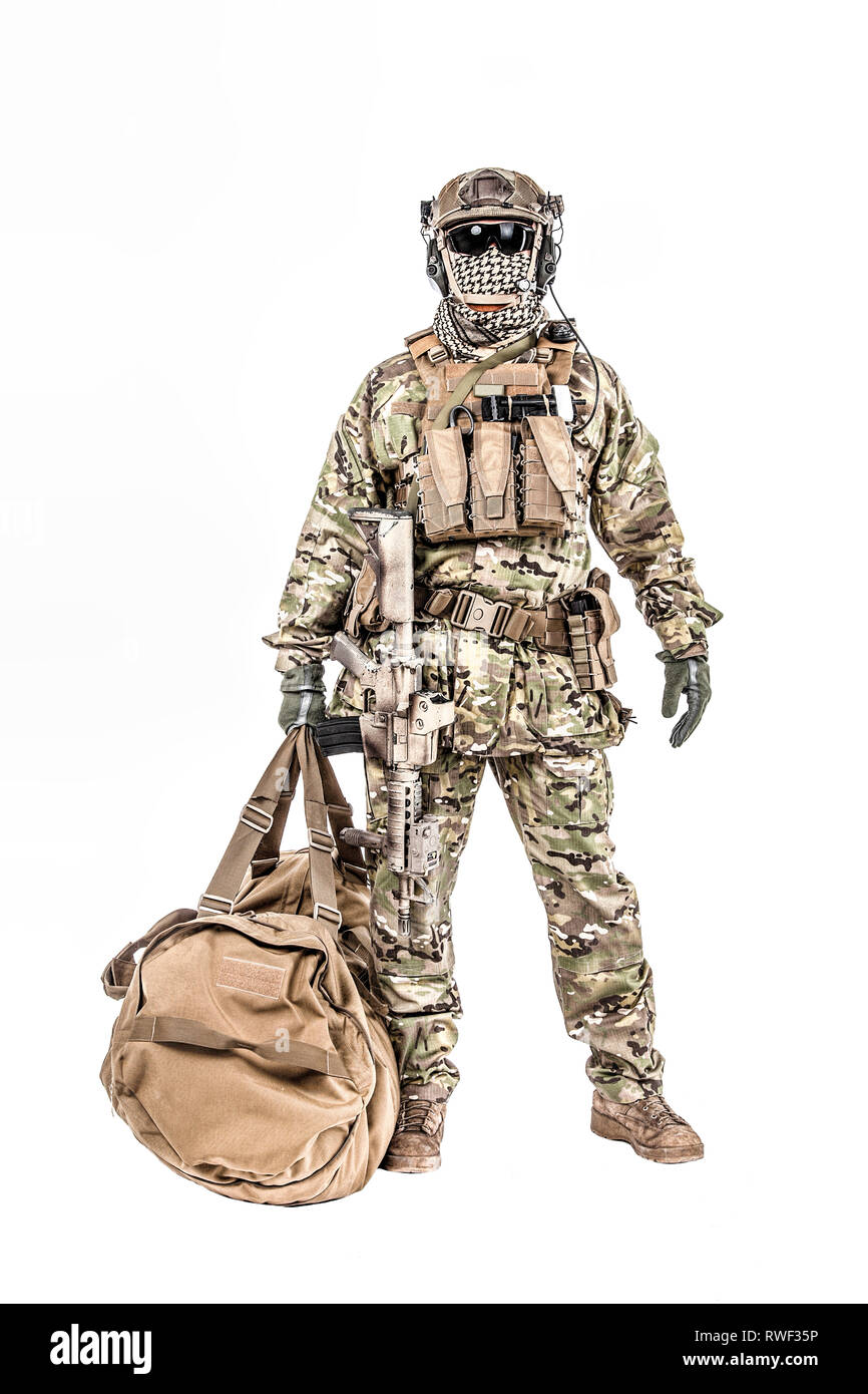 5c543421 Soldier standing with duffel bag, studio shot. - Stock Image