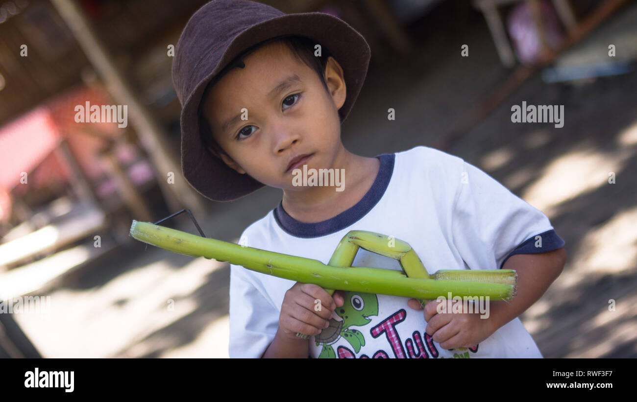 Young Filipino boy with Toy bamboo gun - Antique, Philippines - Stock Image