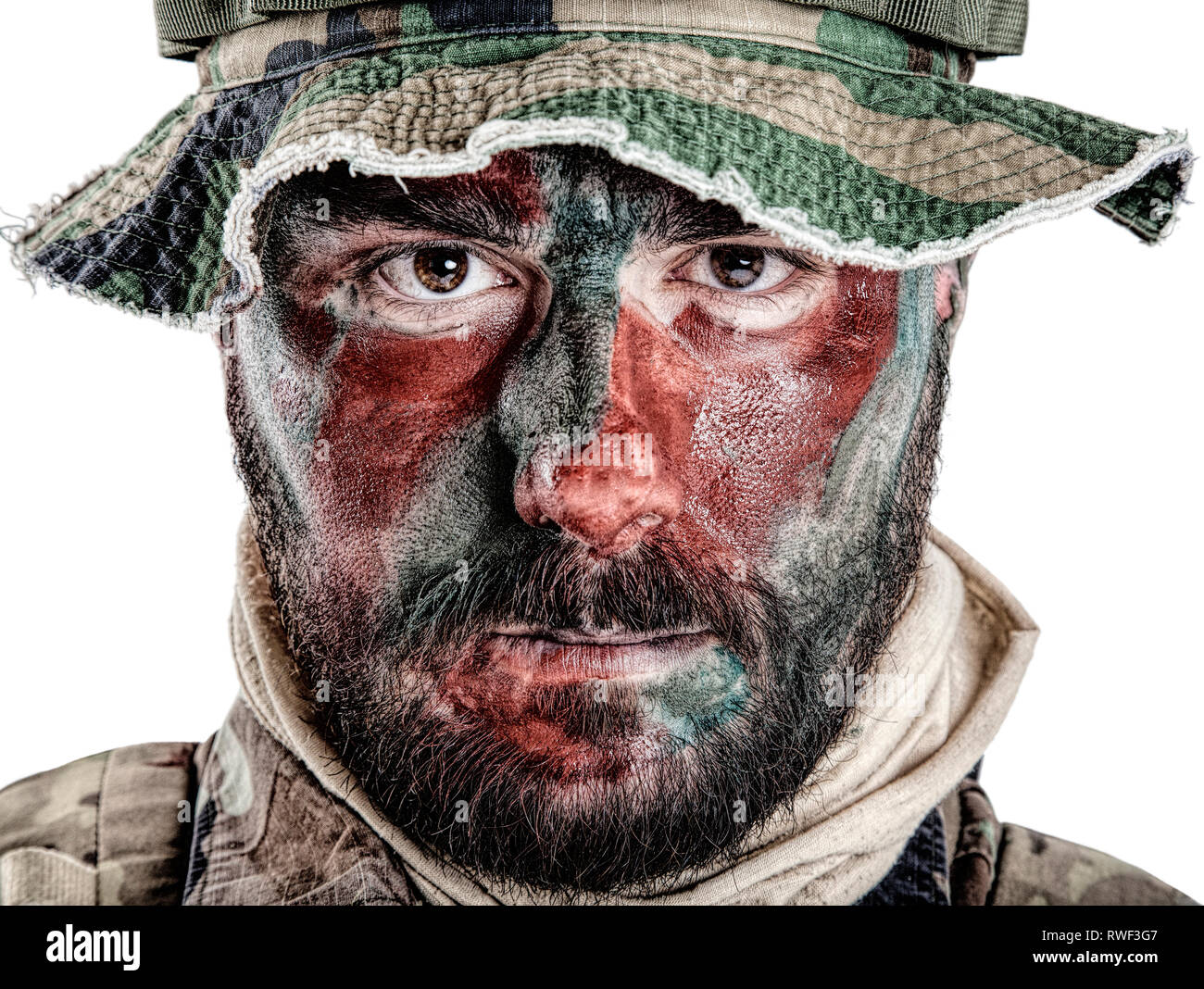e35131faea7f2 U.S. special forces soldier wearing jungle hat with painted red and green  face. - Stock