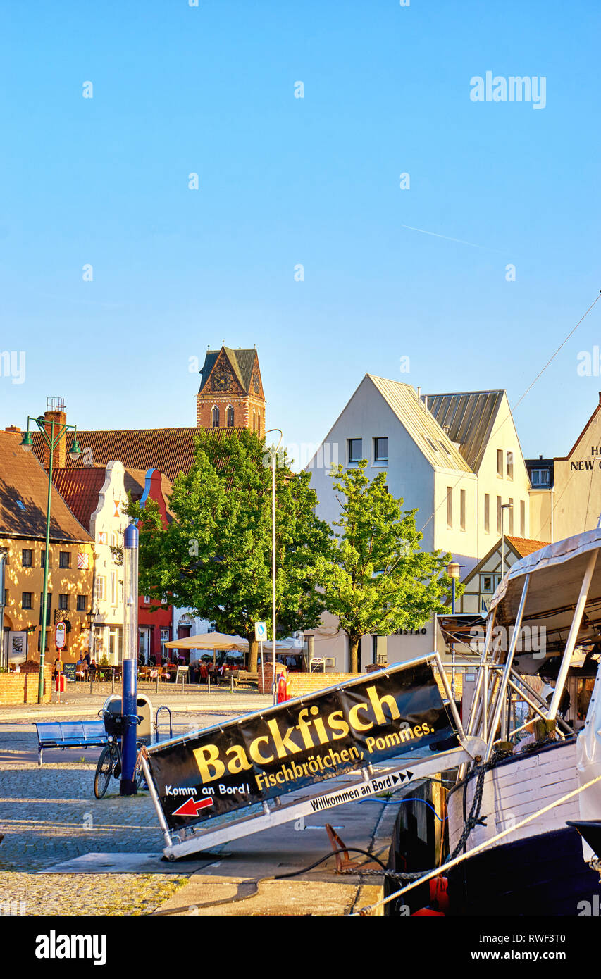 Fishing boat in the old harbor of Wismar. Letters with Backfisch, Fischbrötchen, Pommes means fried fish, fish rolls, French fries. - Stock Image