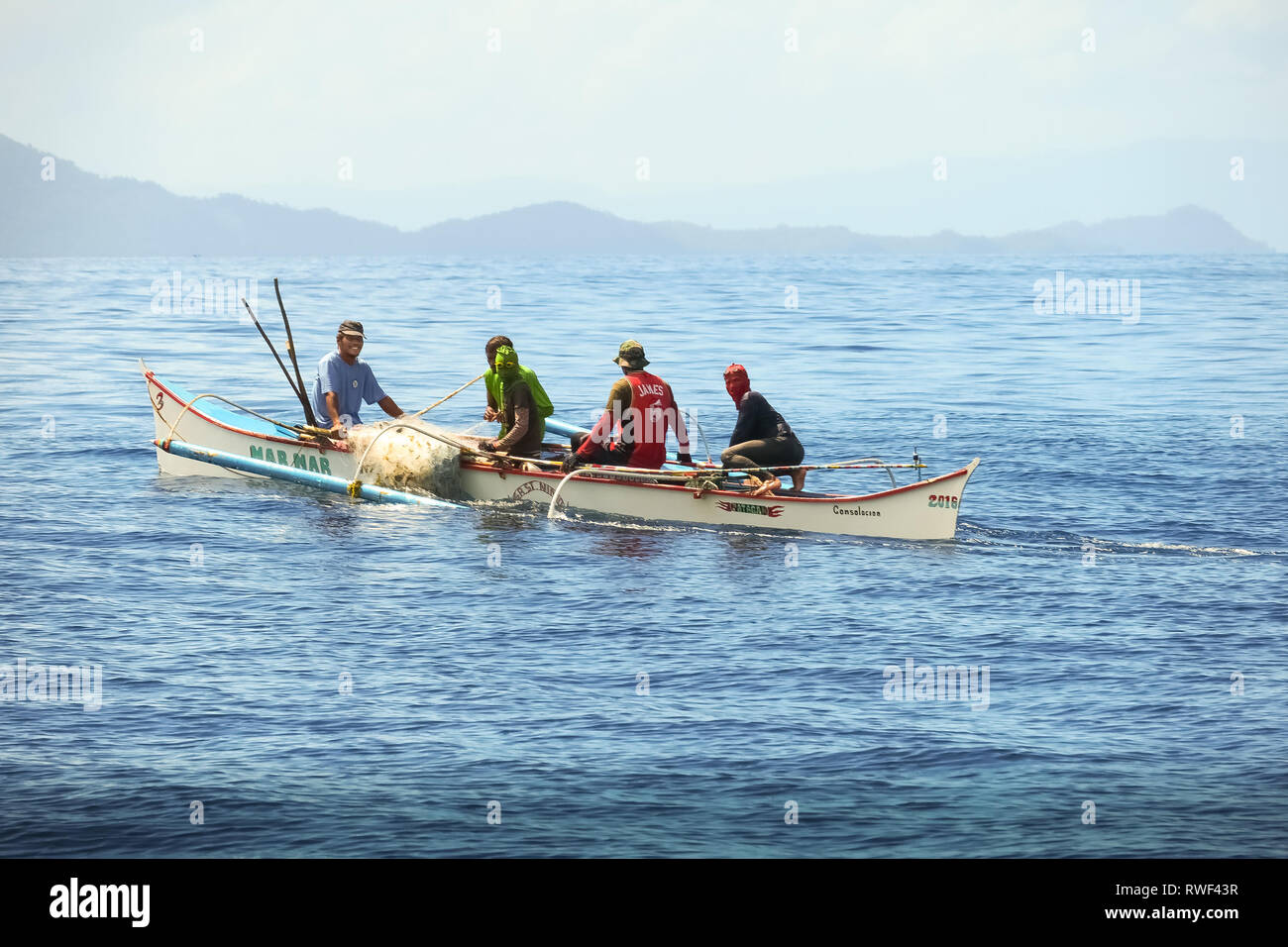 Filipino Fishermen Wearing Masks in Boat With Net - Siargao island, Philippines - Stock Image