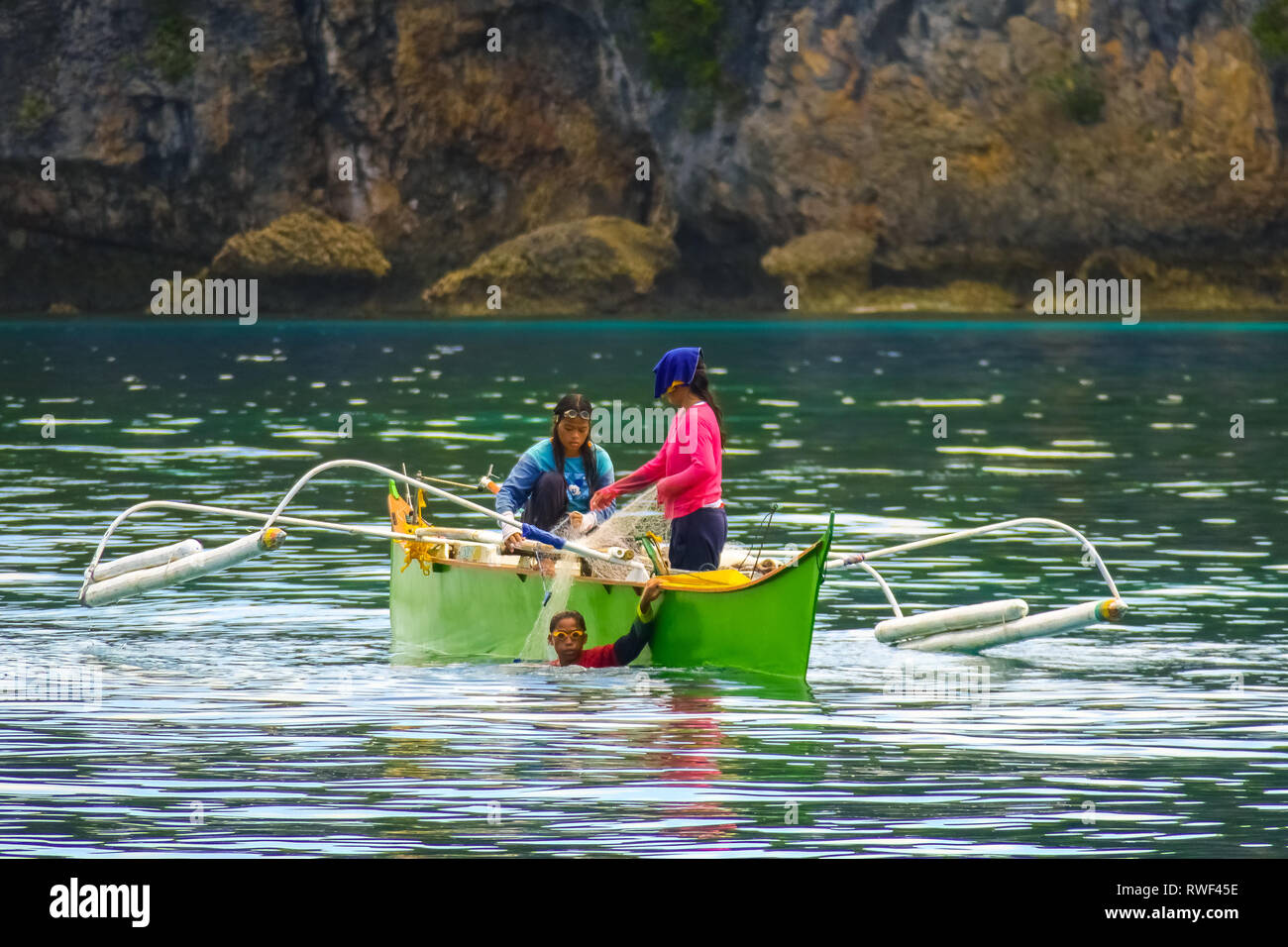 Filipino Boy Wearing Goggles, Diving and Fishing With Women in Green Boat - Siargao, Philippines - Stock Image