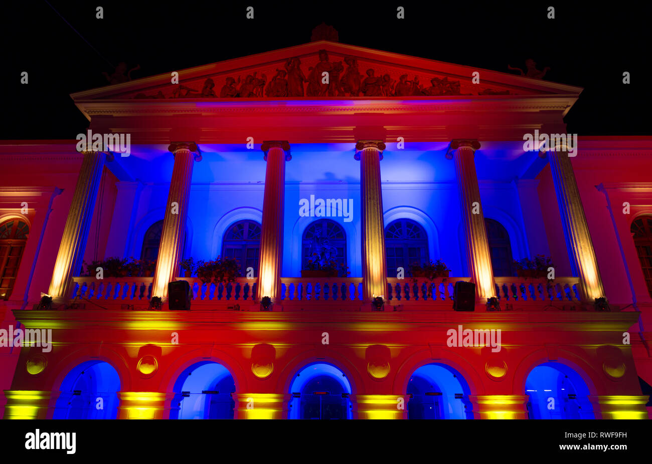 The Sucre theater illuminated with red, yellow and blue colours in the historic city center of Quito, Ecuador. - Stock Image