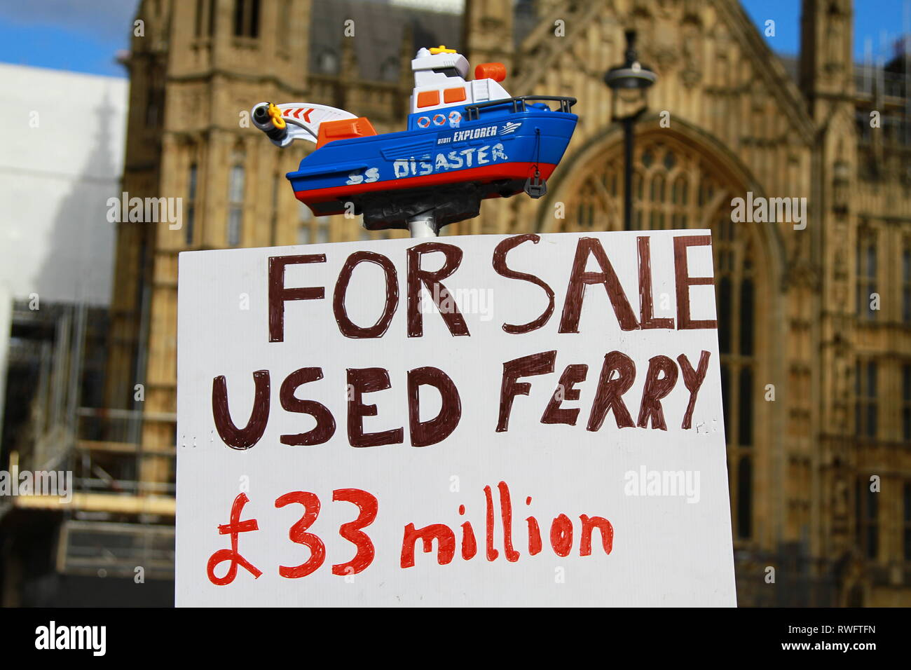 FAILING GRAYLING. FOR SALE USED FERRY 33 MILLION POUNDS SIGN WITH HOUSES OF PARLIAMENT IN BACKGROUND. WASTED TAX PAYERS MONEY. SIGN REFERRING TO MISTAKES MADE BY THE TRANSPORT SECRETARY CHRIS GRAYLING. GOVERNMENT MISTAKES. - Stock Image