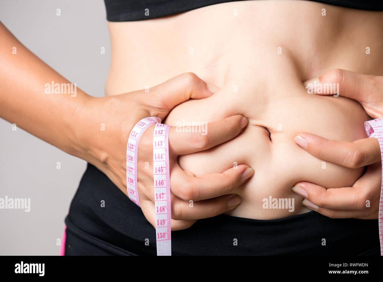 Fat woman hand holding excessive belly fat with measuring tape. Healthcare and woman diet lifestyle concept to reduce belly and shape up healthy stoma - Stock Image