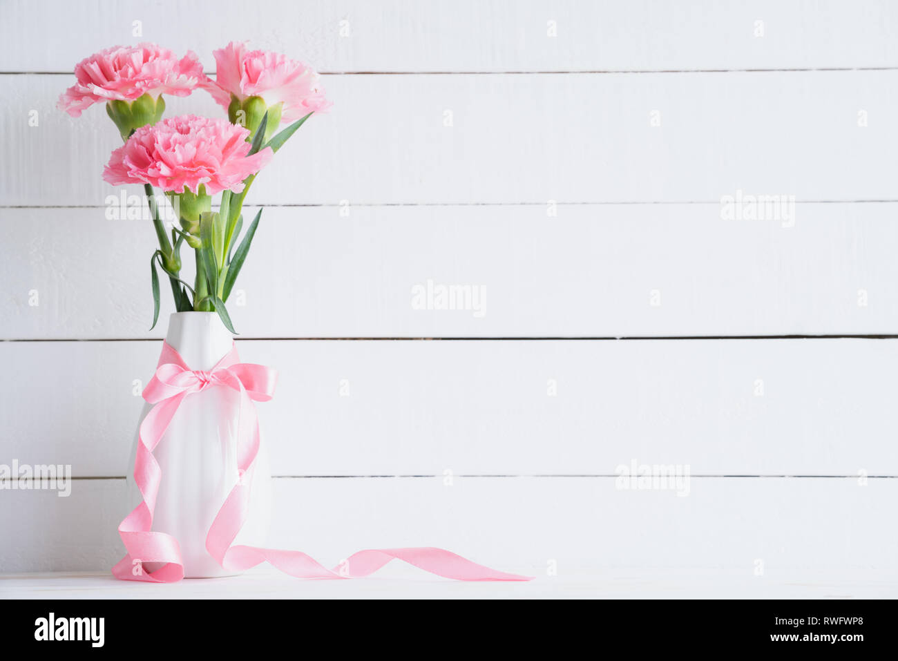 Valentines day and love concept. Pink carnation flower in vase with Wooden letters forming word LOVE written on white background. - Stock Image