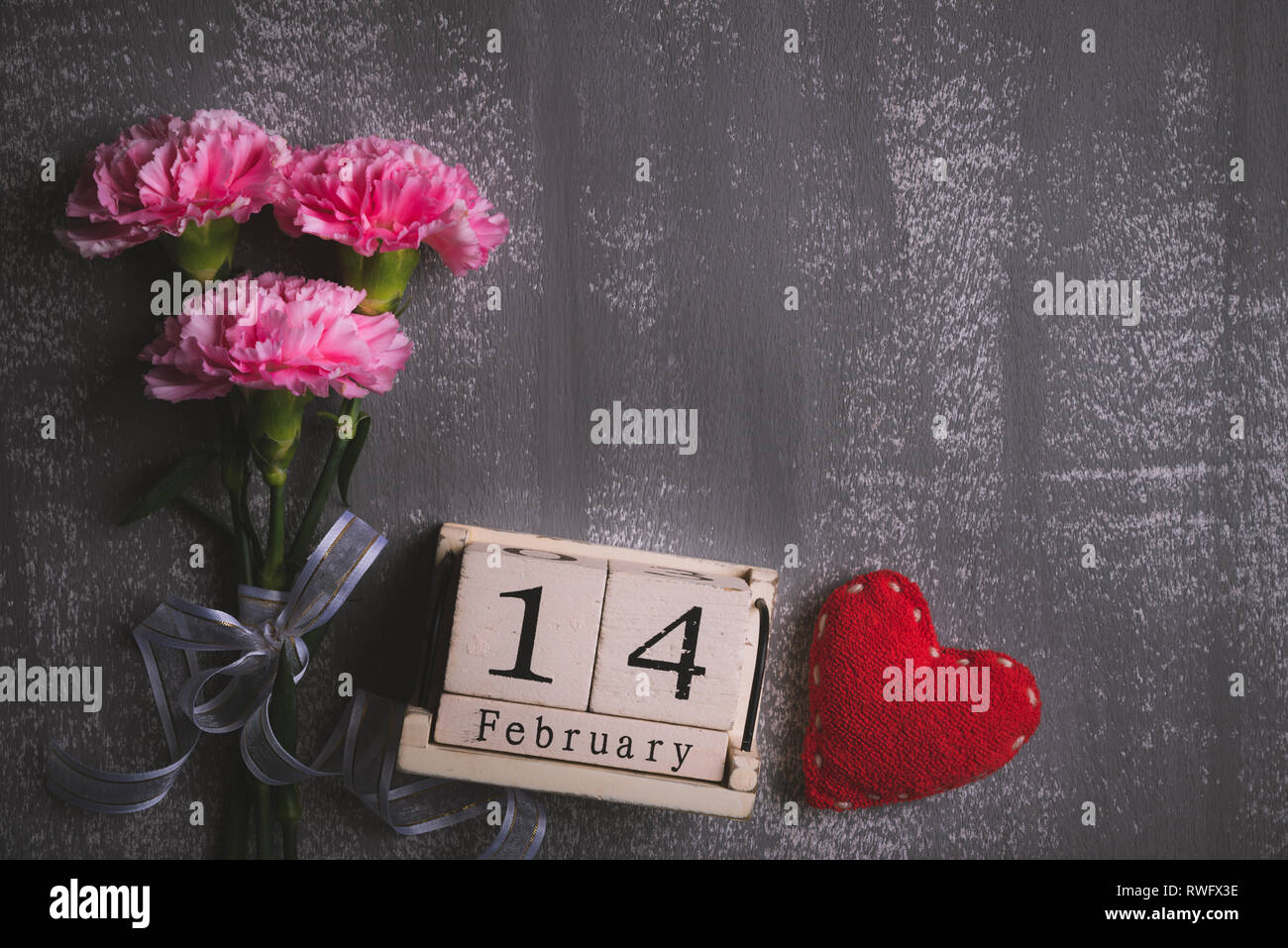 Valentines day and love concept. Pink carnation flower with February 14 text on wooden block calendar and red heart and on gray wooden background. - Stock Image