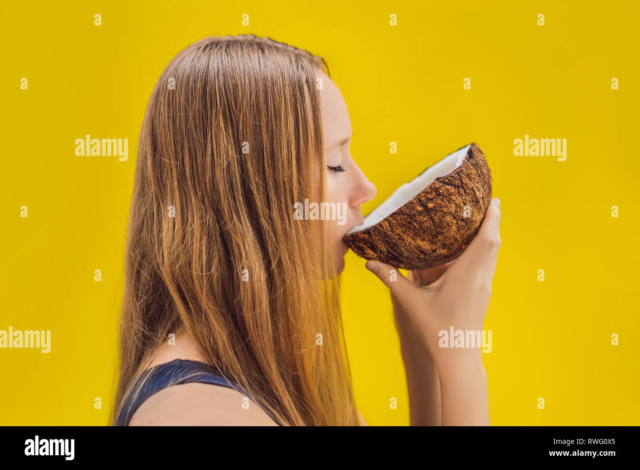 Young woman drinking coconut milk on Chafrom coconut on a yellow background - Stock Image