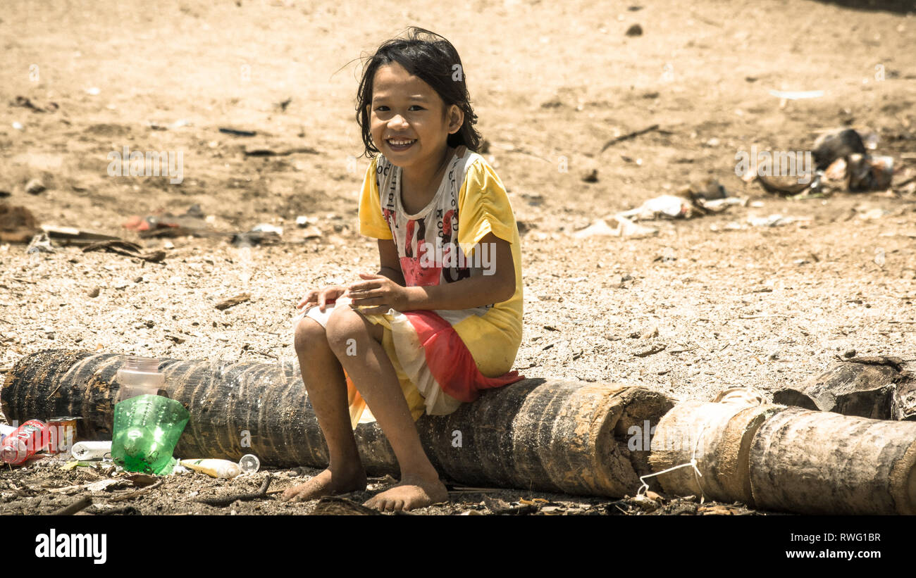Friendly smiling Filipino girl on village beach - Sorsogon, Philippines - Stock Image