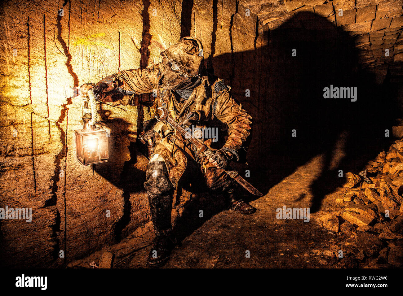 Underground post apocalyptic creature with homemade weapons and lantern. - Stock Image