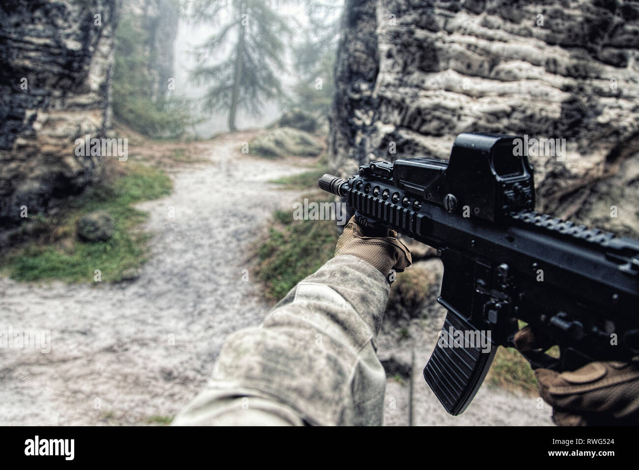 First person view of a private military contractor in action in the rocks. - Stock Image