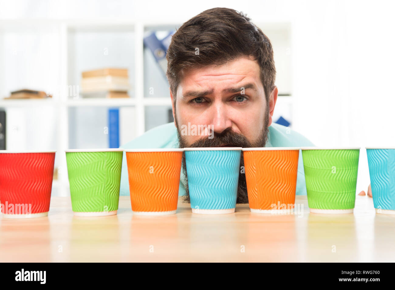 Choose from alternatives. Man bearded choosing one of lot colorful paper cups. Alternative concept. Pick one. Diversity and recycling. Eco paper cup. Coffee to go paper cup. How many cups per day. - Stock Image