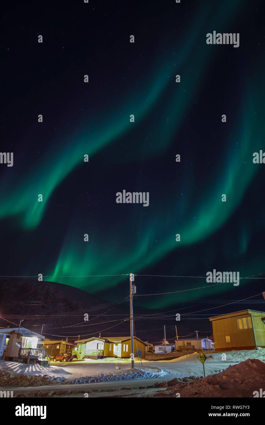 Aurora Borealis dancing over homes in Pangnirtung - Stock Image