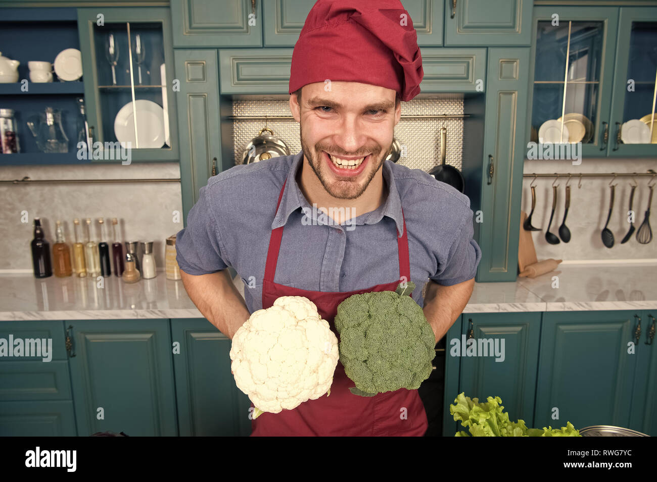 Substitute carefully. Although substitutions seem obvious they can be tricky business. Ruined dish is waste of time. Man chef substitutes broccoli with cauliflower. Chef smiling knows kitchen tricks. - Stock Image