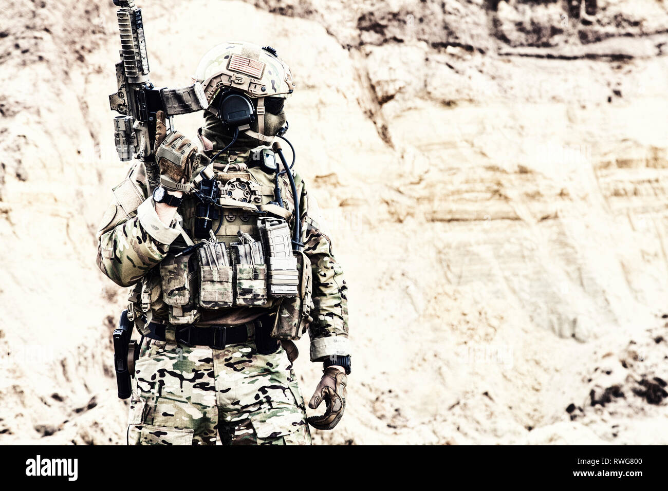 Elite fighter of special forces standing with service rifle, ready for battle. - Stock Image