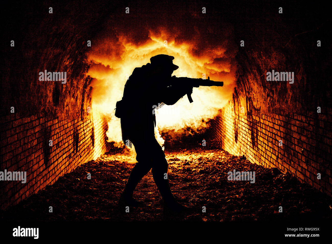 Silhouette of post apocalyptic soldier shooting weapon in underground sewage tunnel. - Stock Image