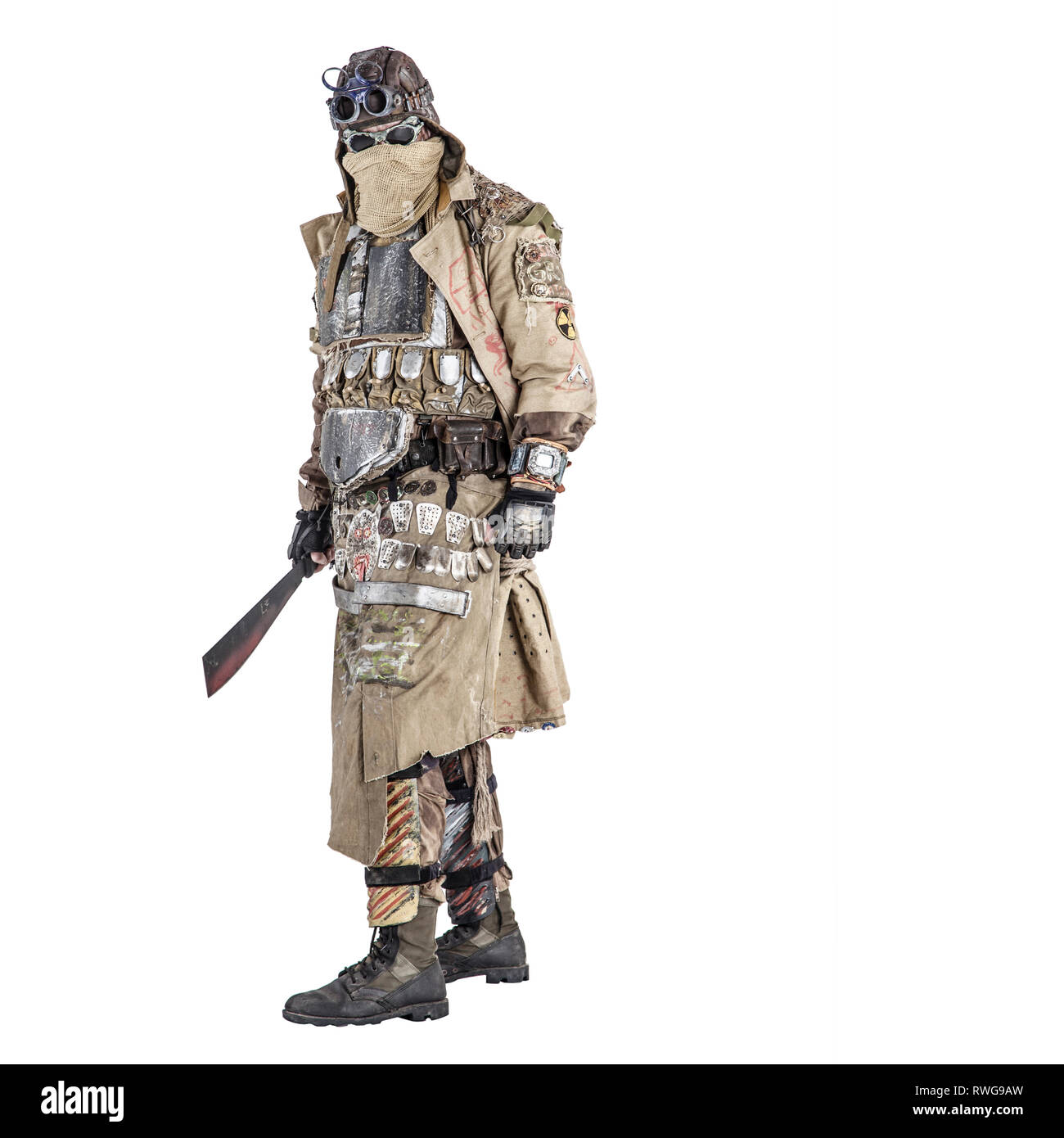 Scary post apocalyptic survivor in handmade armored clothes, armed with machete. - Stock Image