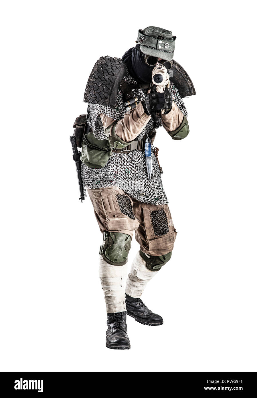 Post apocalyptic soldier wearing handmade armor, aiming submachine gun. - Stock Image