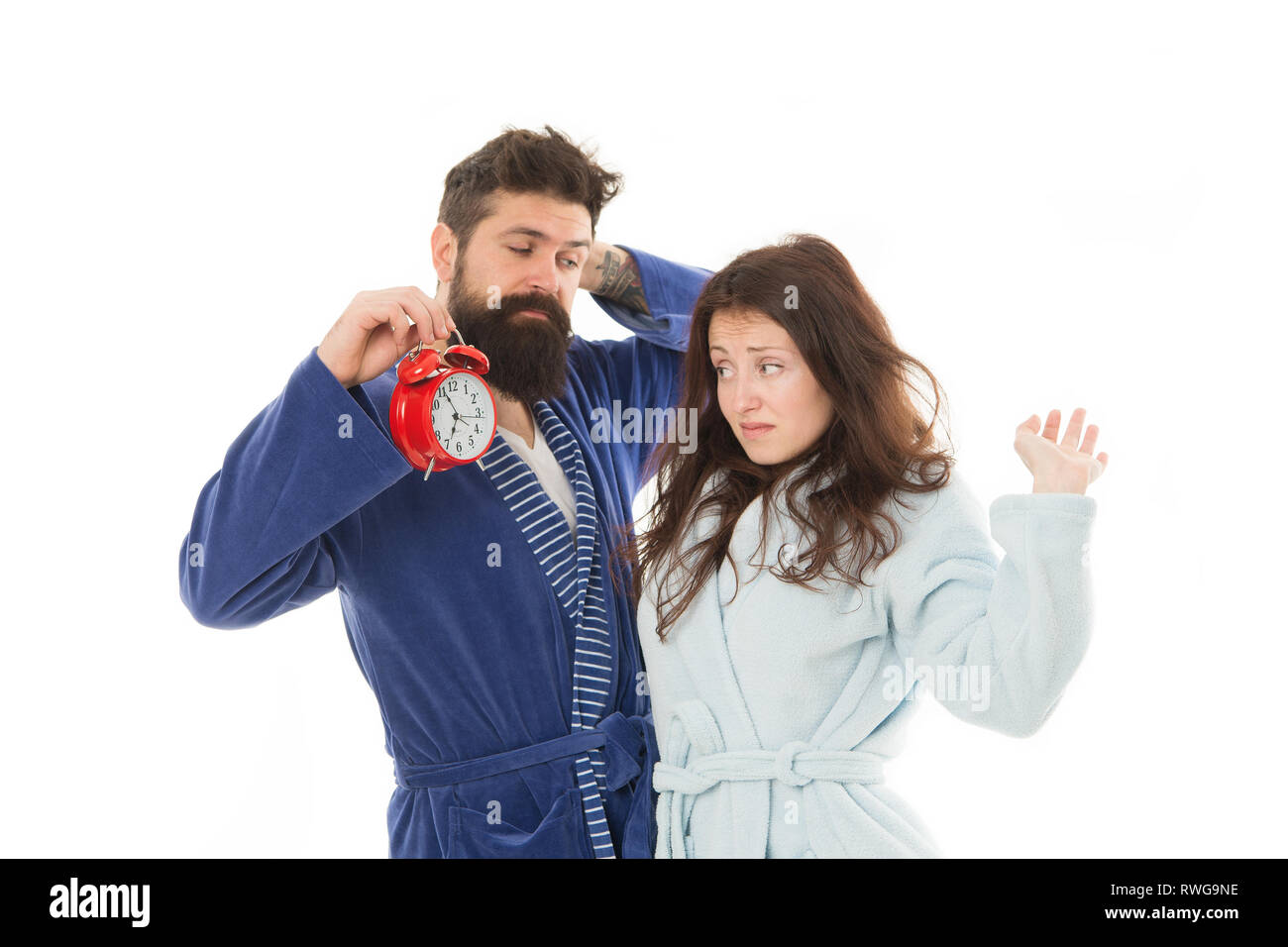 Family morning. Perfect morning concept. Family woke up on time. Couple in love young family in bathrobes stand isolated on white background. Girl with tousled hair and man with clock in hand. - Stock Image