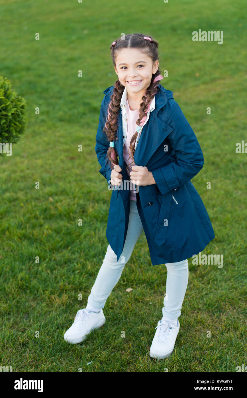 Fashionable coat. Girl cute face braided hair posing coat in spring park. Clothing for spring walks. Little fashion model. Clothes and accessory. Kid wear trench coat. Spring coat. Must have concept. - Stock Image