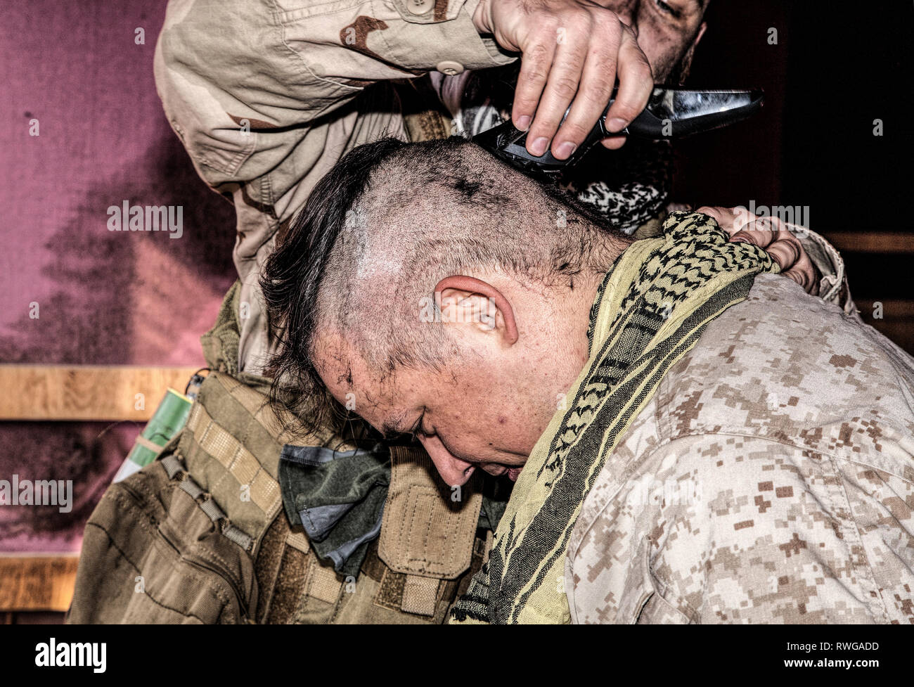 U.S. Marine shaving friends head with clipper. - Stock Image