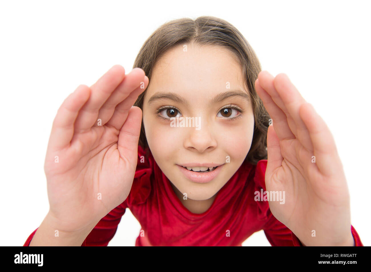 Let me look closer. Kid girl long healthy shiny hair on white background isolated. Little girl with long hair looking at you with attention. Kid happy cute face with adorable curly hair close up. - Stock Image