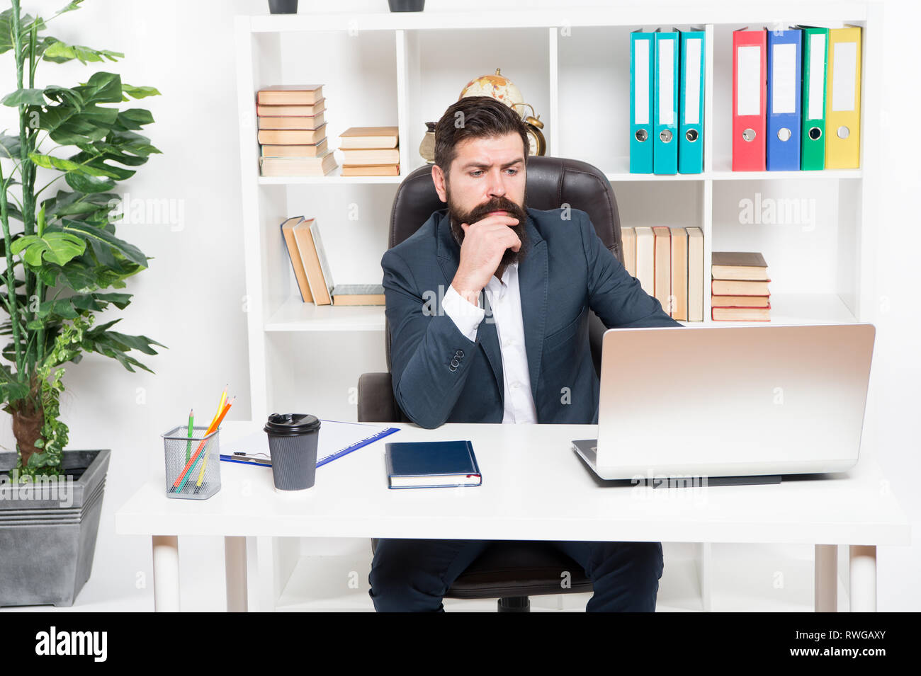 Broker tracks financial indicators. Man bearded hipster boss sit in leather armchair office interior. Boss at workplace. Manager formal corporate style working. Business people. Busy boss in office. - Stock Image