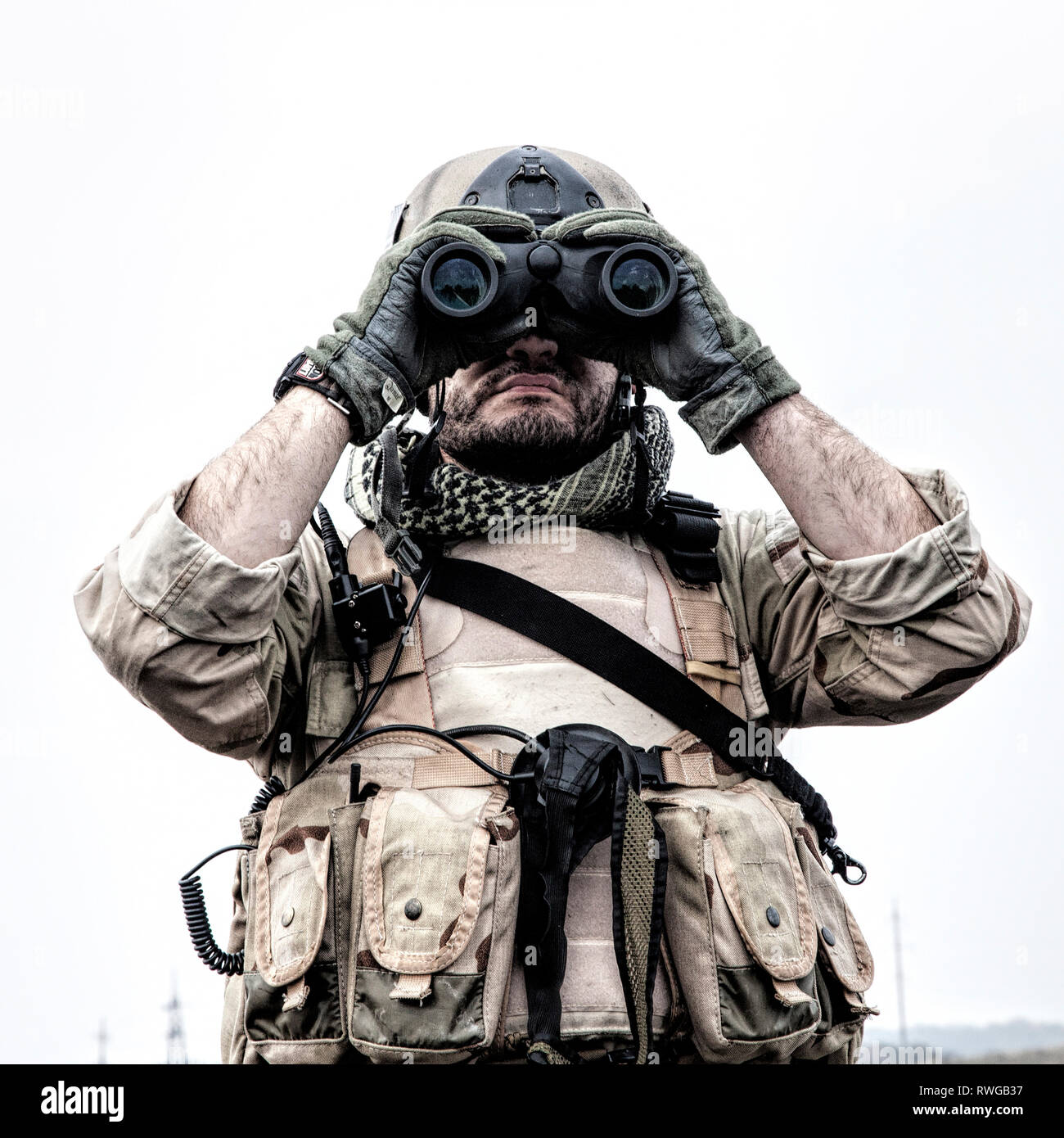 Navy SEAL scout looking through binoculars to observe terrain and search for enemy targets. - Stock Image