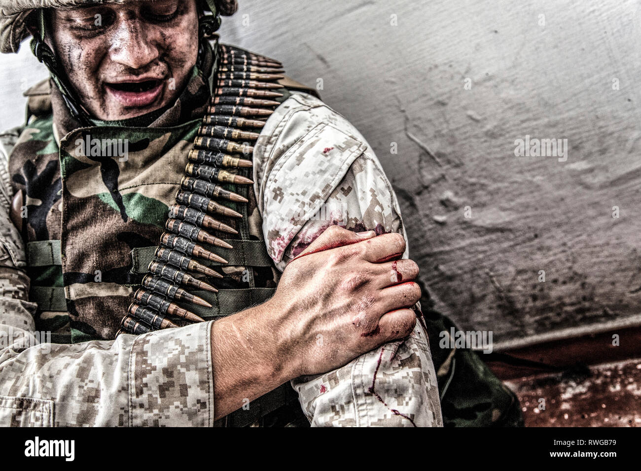 Soldier clamping his gunshot wound with healthy hand to try and stop bleeding. - Stock Image