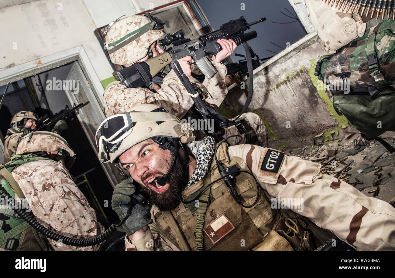 Special forces team leader screaming into tactical radio handset while under enemy fire. - Stock Image